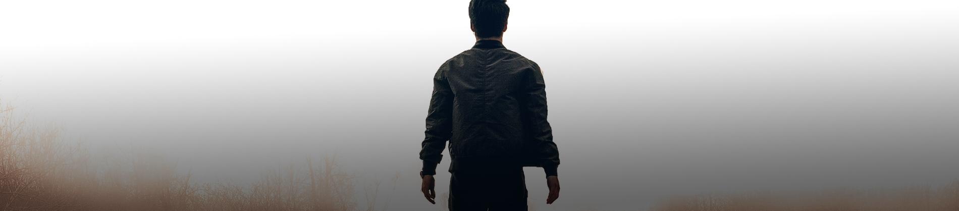 A man stood in a field looking towards fog