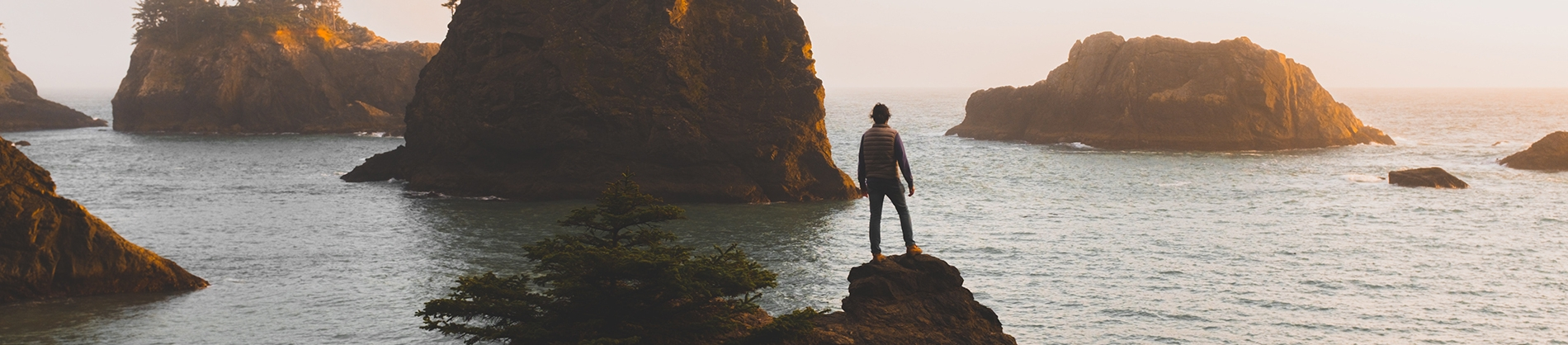 A man stood on a rock overlooking the ocean