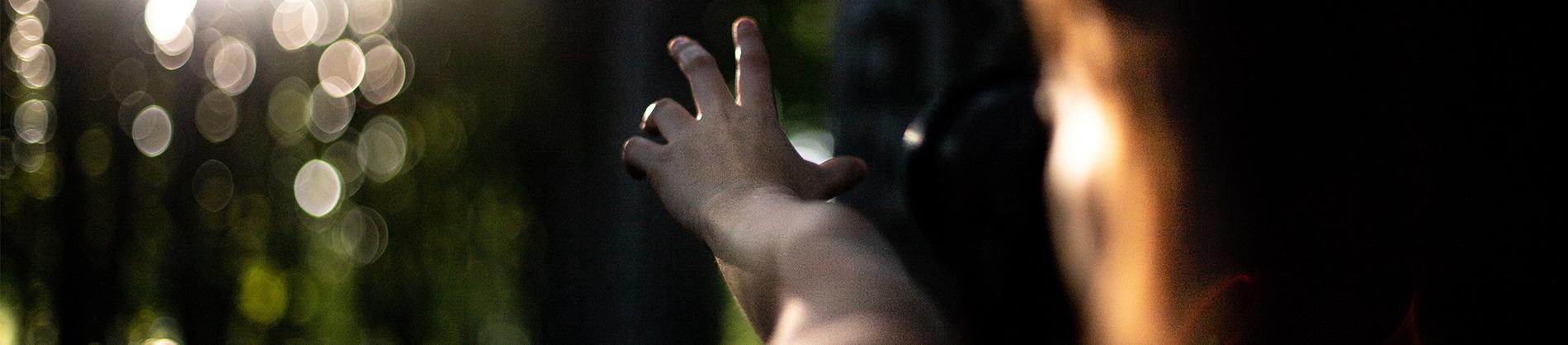 A person reaching their hand forward towards the sun