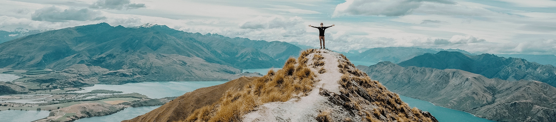 A man stood on top of a grassy cliff with his arms out wide