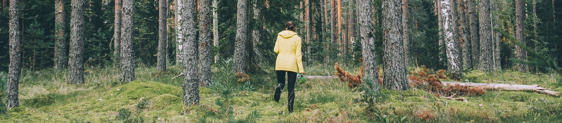 A women in a yellow coat running through a forest