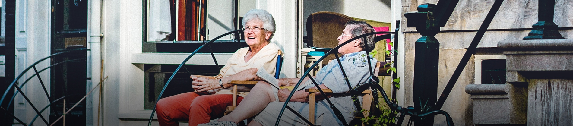 An elderly couple sat on chairs outside their home