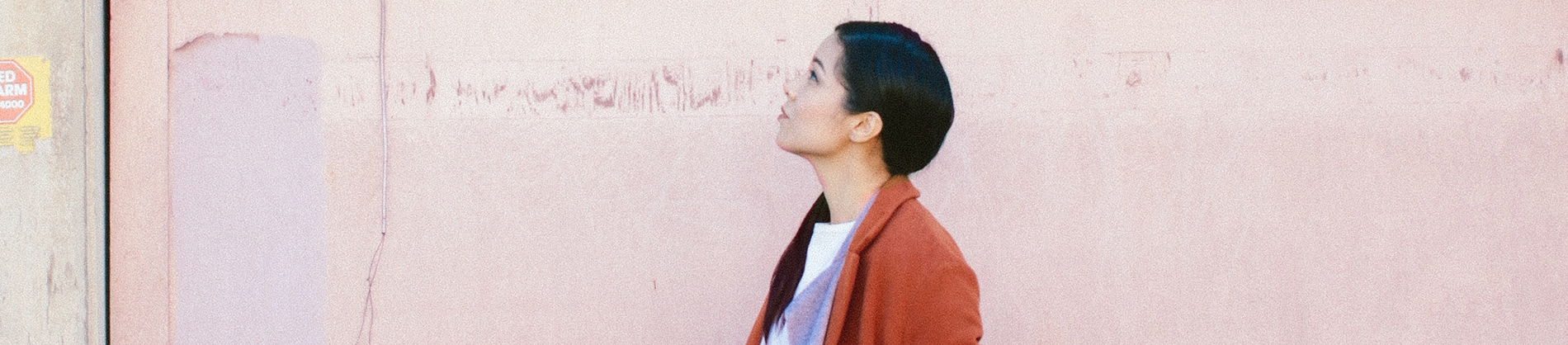 A women stood against a pink wall looking up to the sky