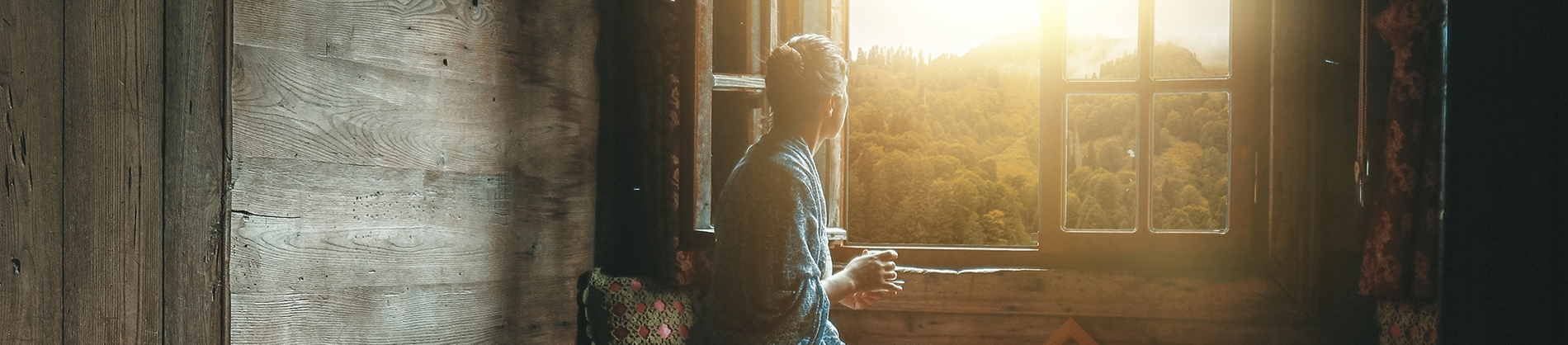 A women sat looking out of a wooden cabin window