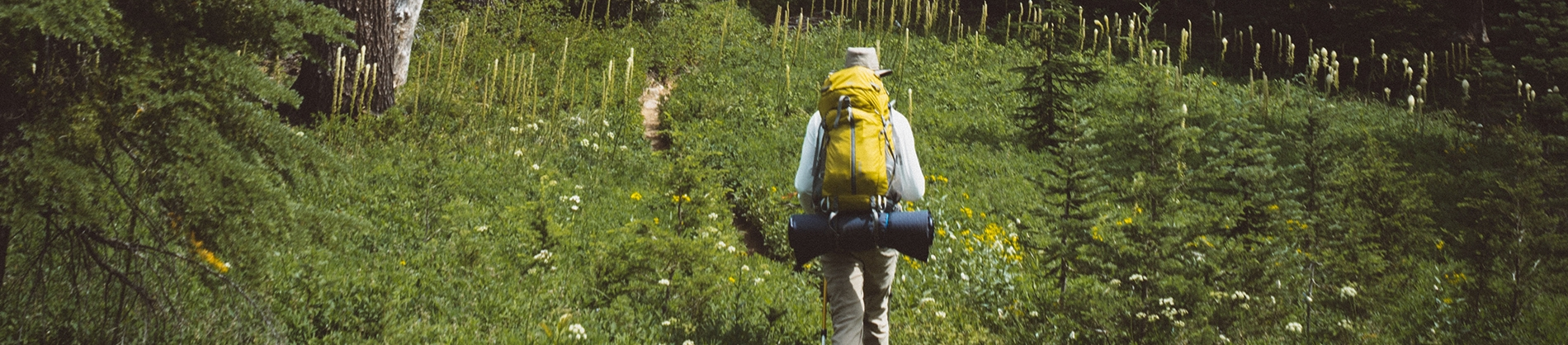 A person walking through grass with a backpack on