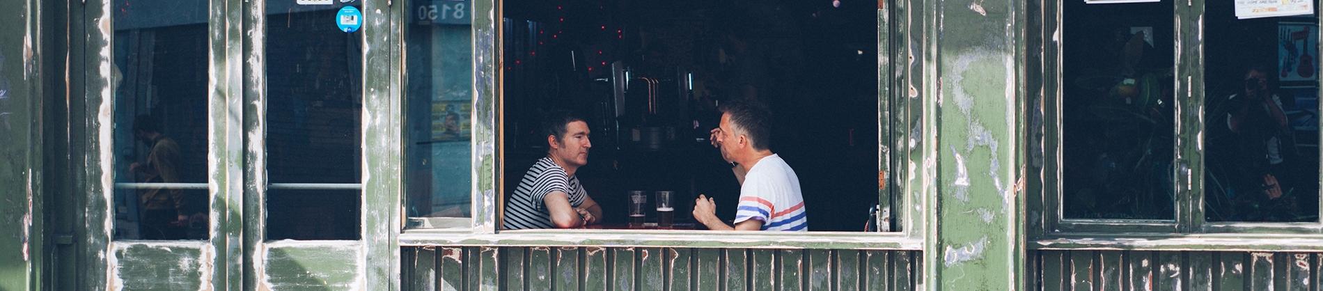 Two men sat in a pub talking