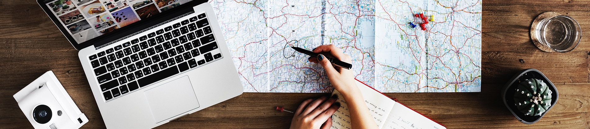 A map open across a wooden table with a laptop and camera at the side