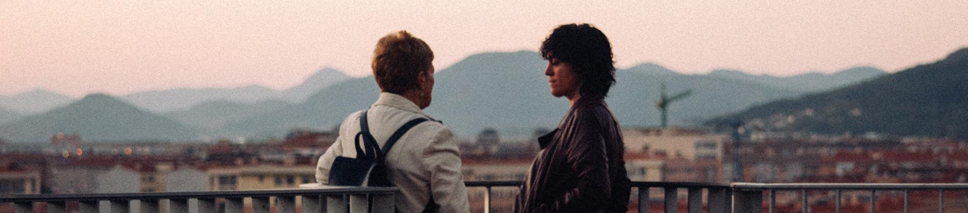 Two women stood on a balcony talking