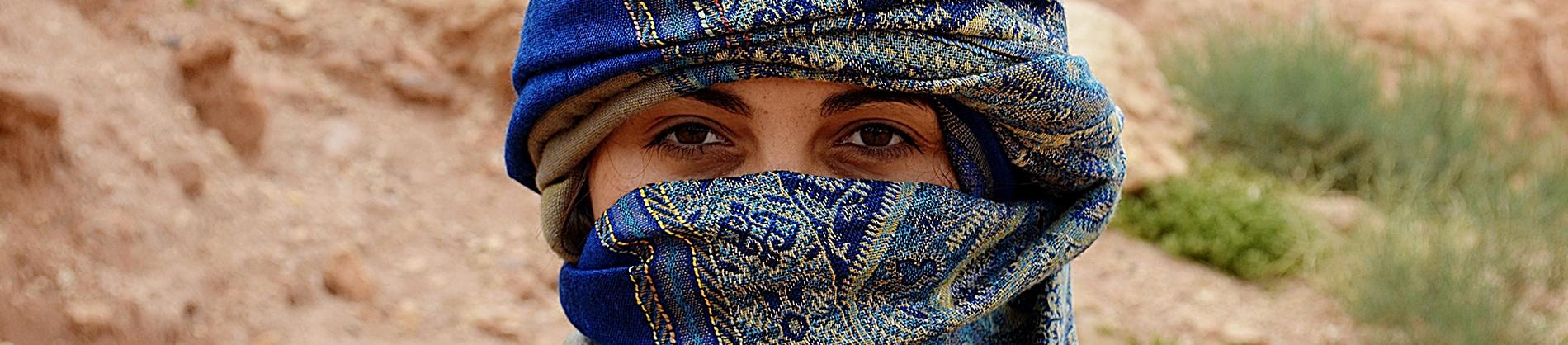 A women wearing a blue head scarf stood in the desert