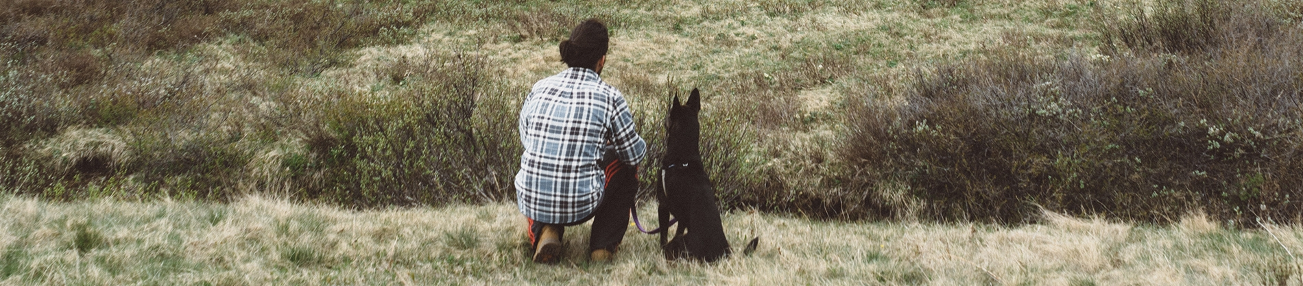 A man and his dog kneeling in a field