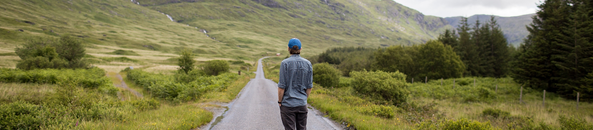 A man looking back on a long path in a valley