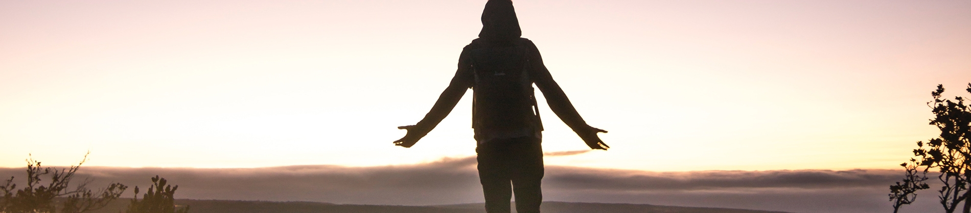 A person stood with their arms open wide looking towards a sunrise