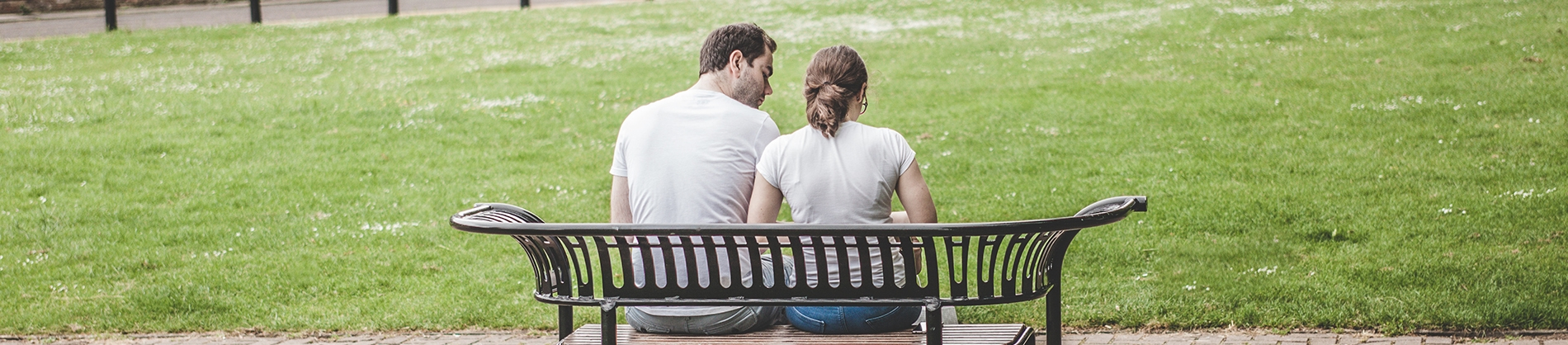 Two people sat on a park bench