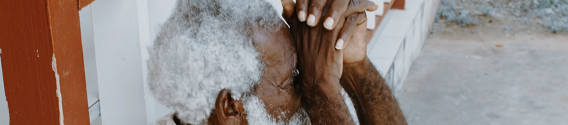 Elderly man with his hands together up to his face
