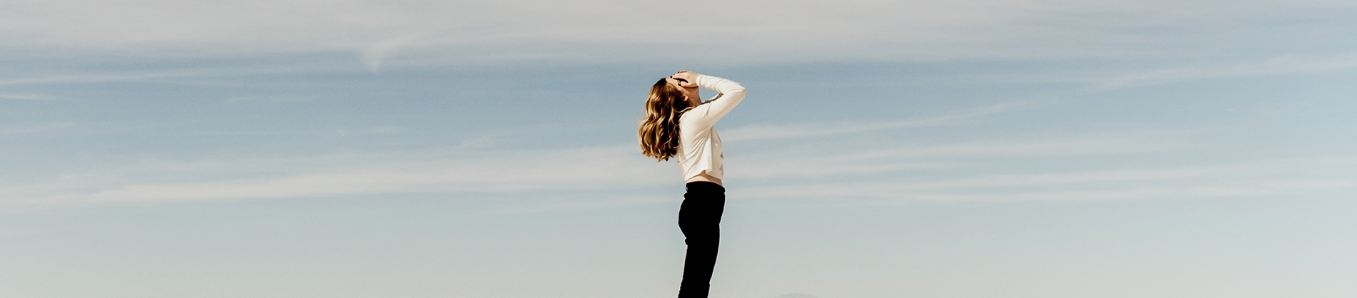 A women with her hands over her face, with blue sky behind her