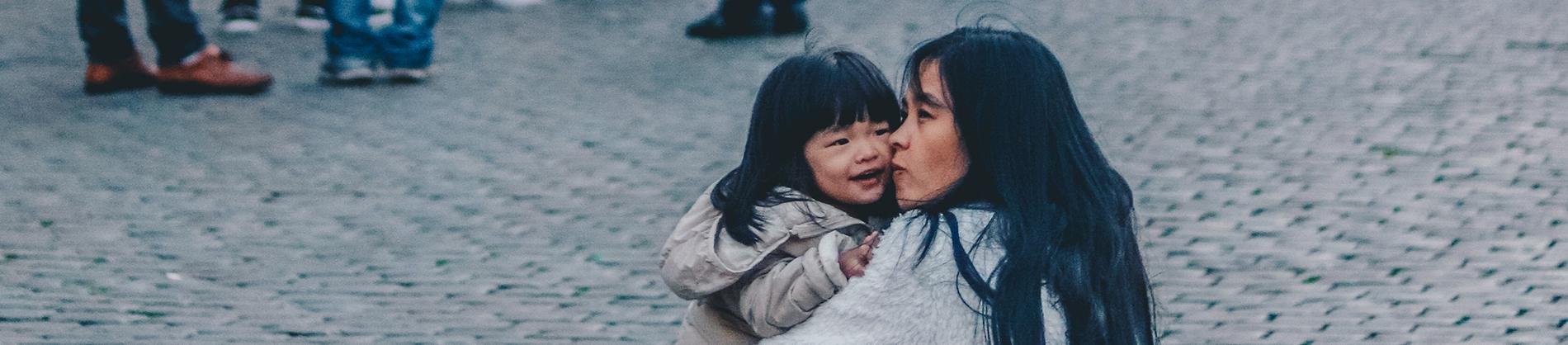 A mum crouching on the pavement cuddling her child