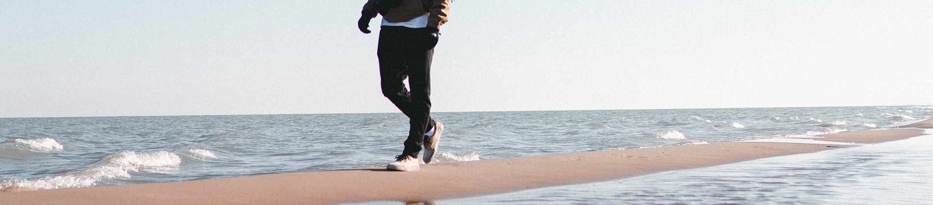 A guy walking along the sand next to the ocean
