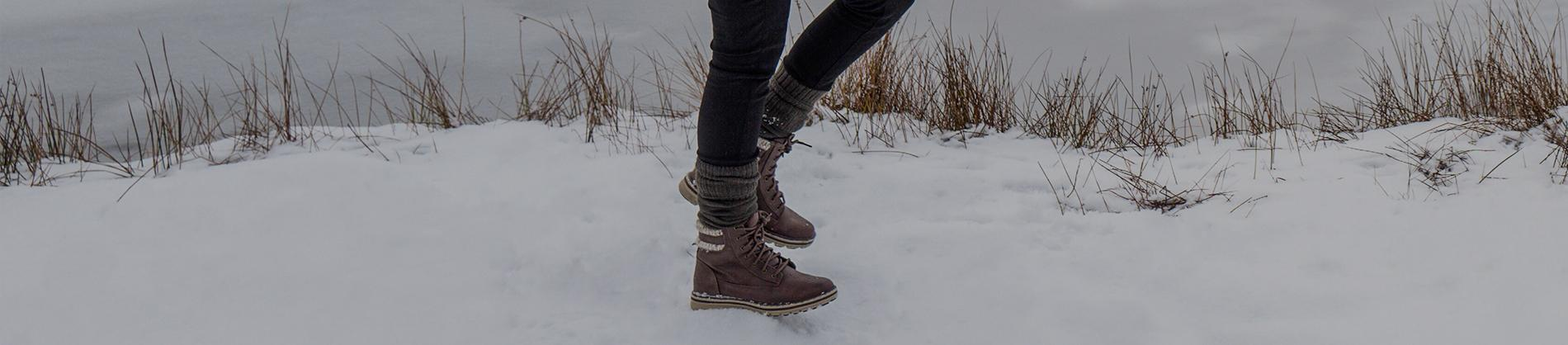 Girl walking in boots through snow