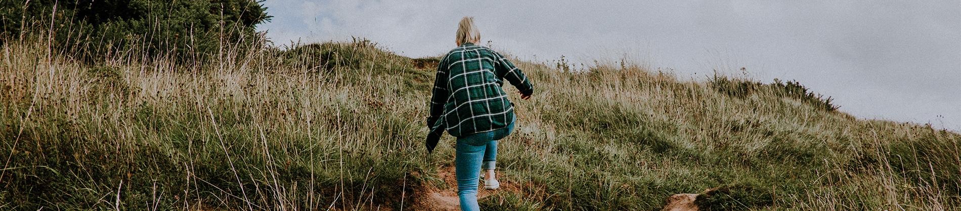 A women climbing up a grassy hill