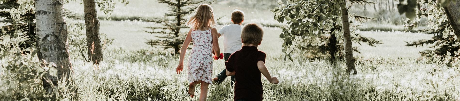 Three children running through a sunny forest