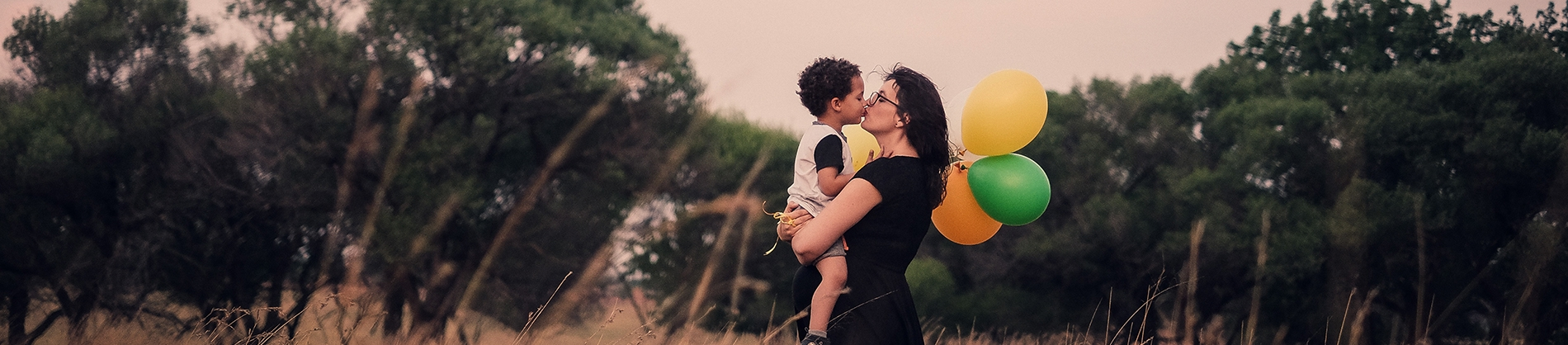 A mother and sun with balloons in a field
