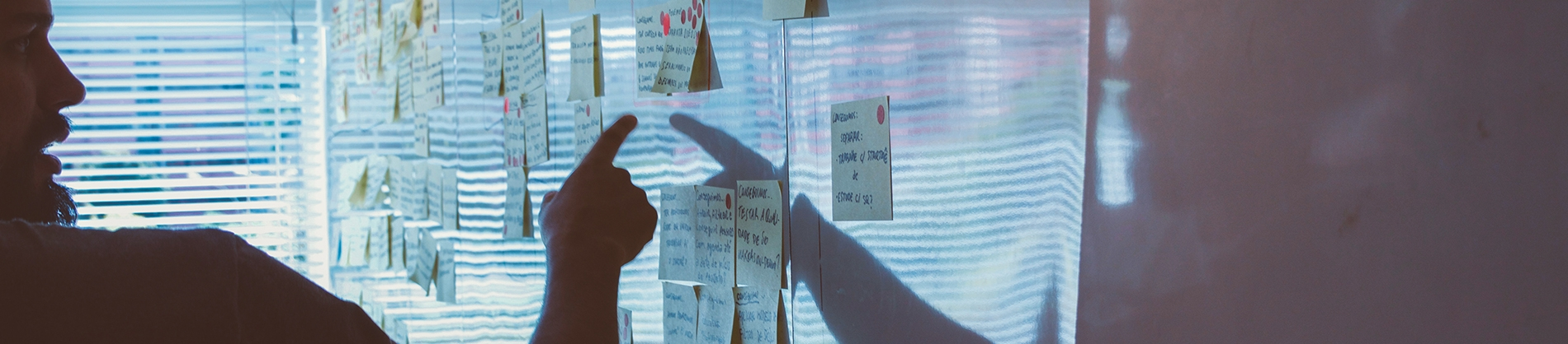 A man pointing at post-it notes on a whiteboard