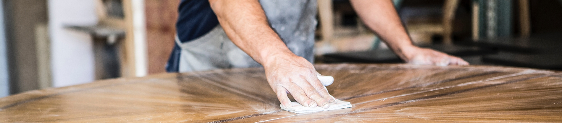 A man sanding down a wooden table
