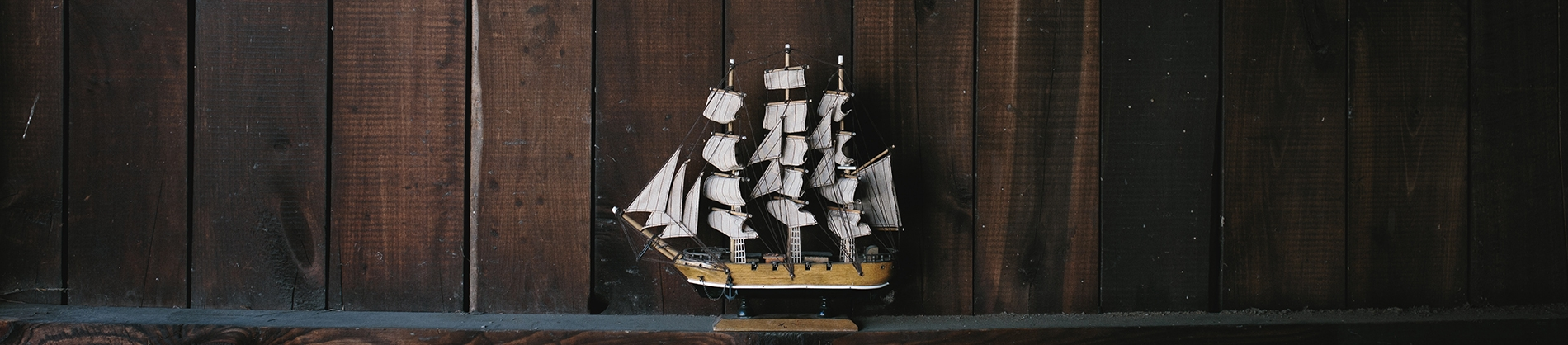 A replica of a ship with a wooden wall behind