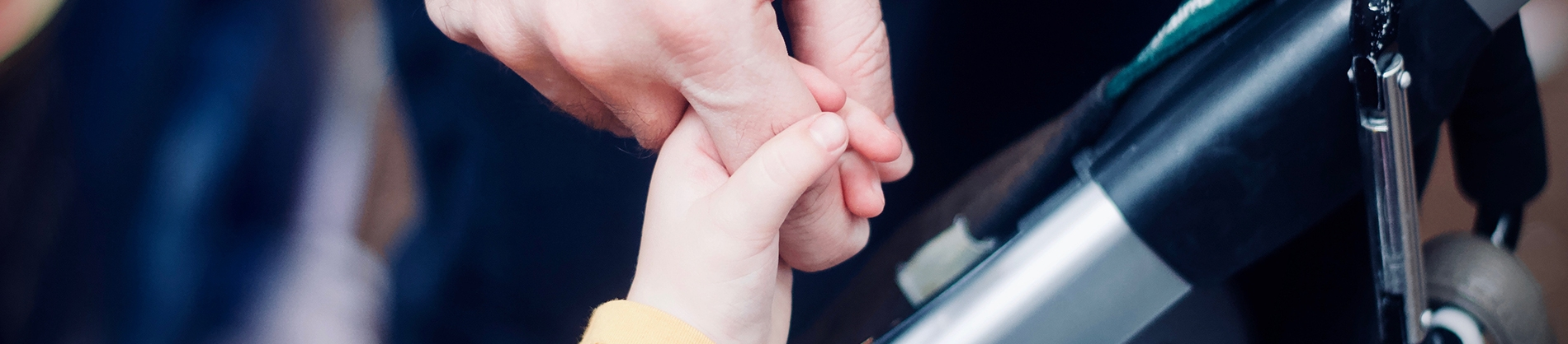 A child holding onto a parents finger