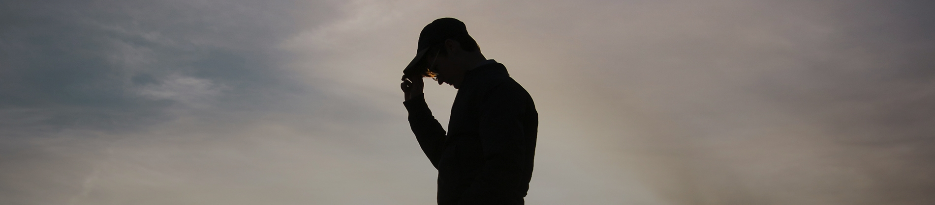 A silhouette of a man wearing a cap