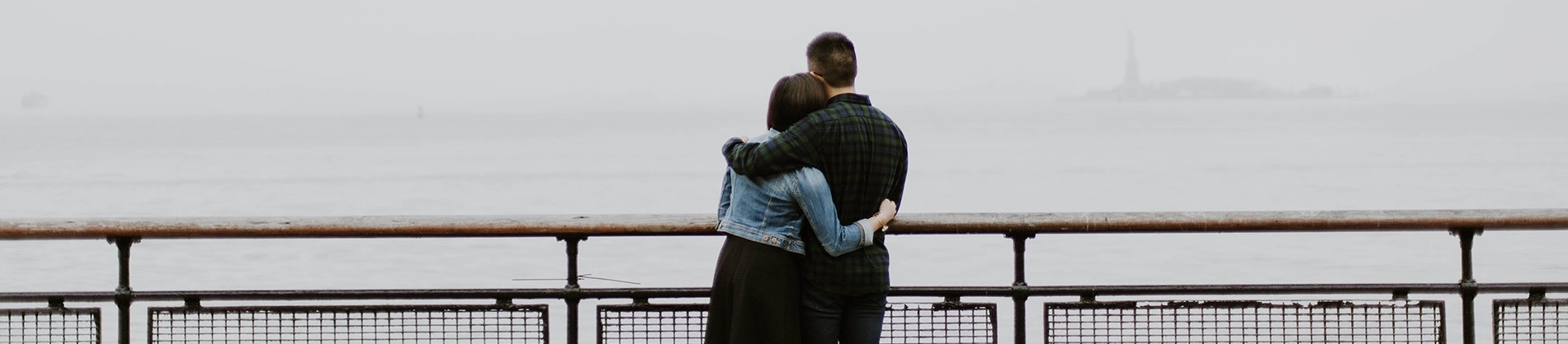 A couple hugging while looking out over railings to the sea