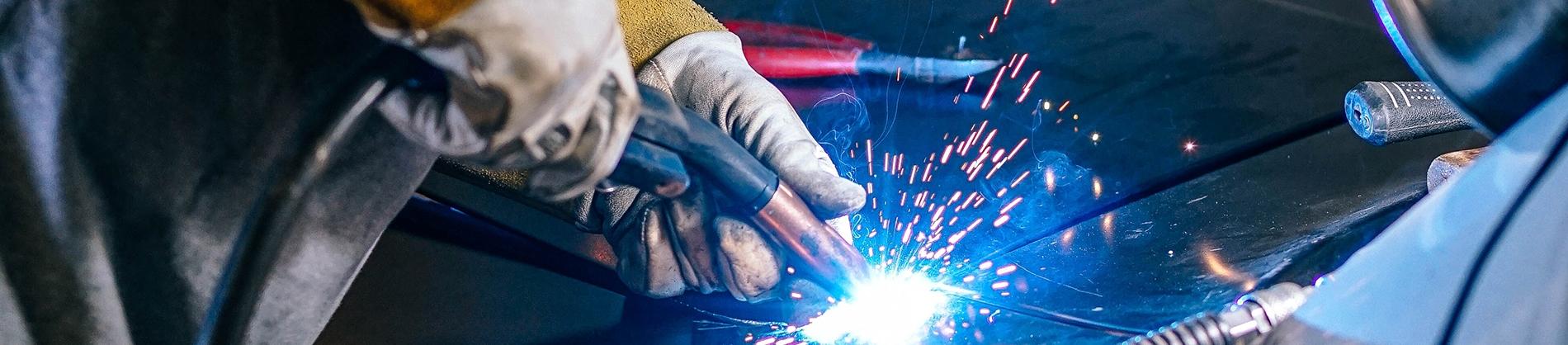 A car mechanic using a power tool on a car