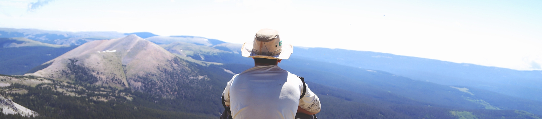 A man in a white hat sat looking over a mountain landscape