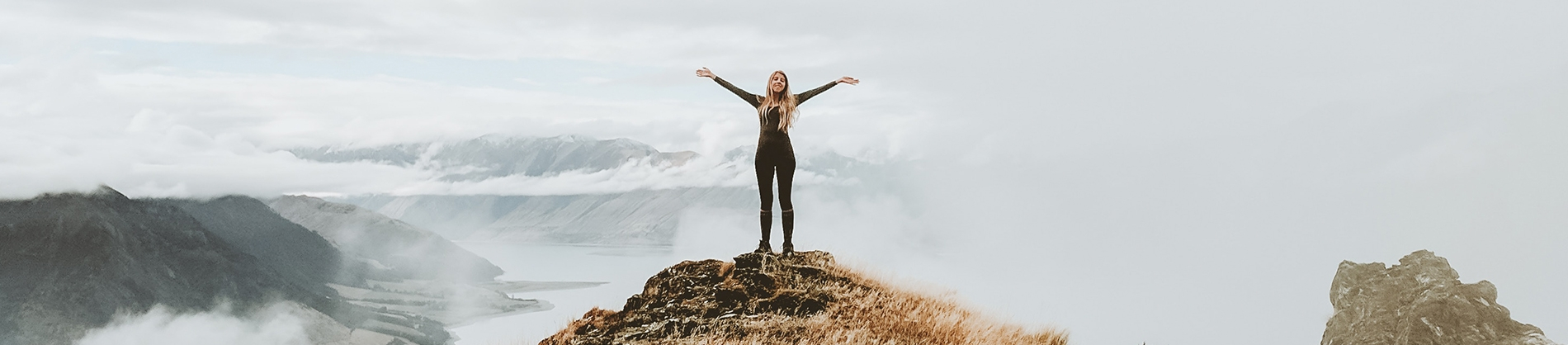 A women stood on a hill with her arms out wide