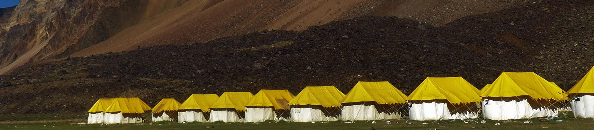 White and Yellow tents lined up on a mountain side