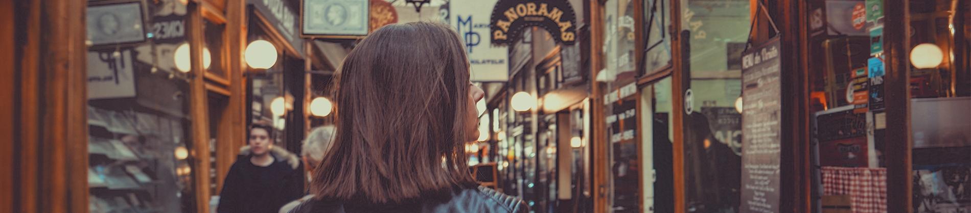 Women walking down a street of shops looking in the windows