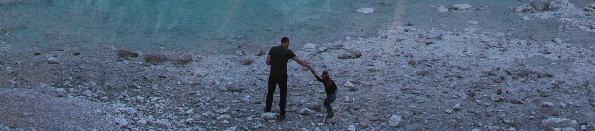 A father and son on the beach. The child is holding the fathers hand and jumping over rocks