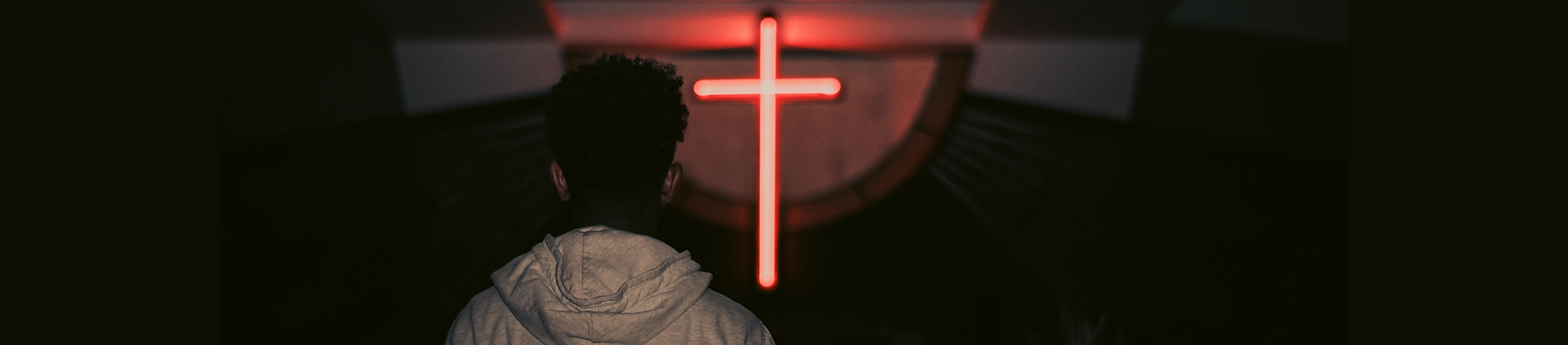 A person looking at a red neon cross on a wall