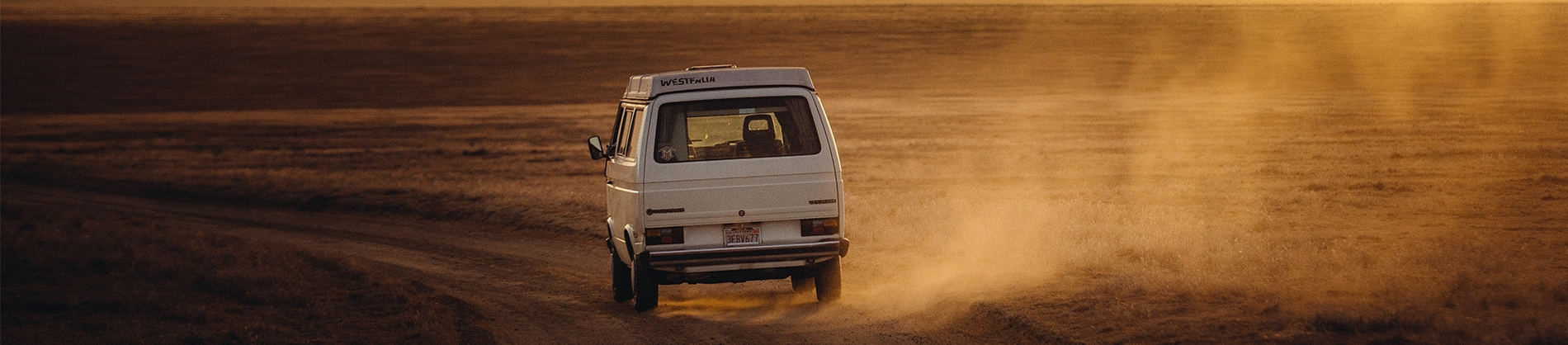A old van driving through the desert