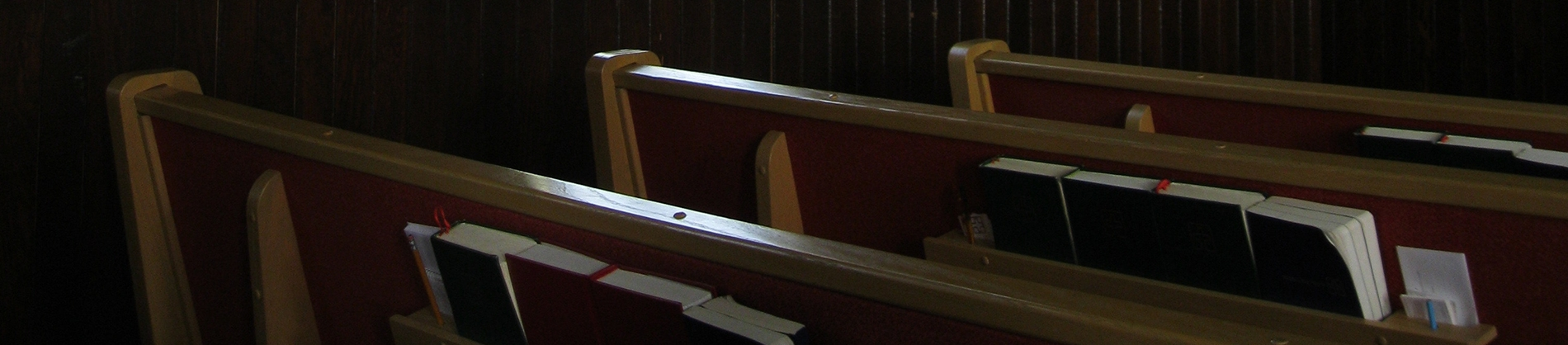 Church pews with bibles stacked in the shelf