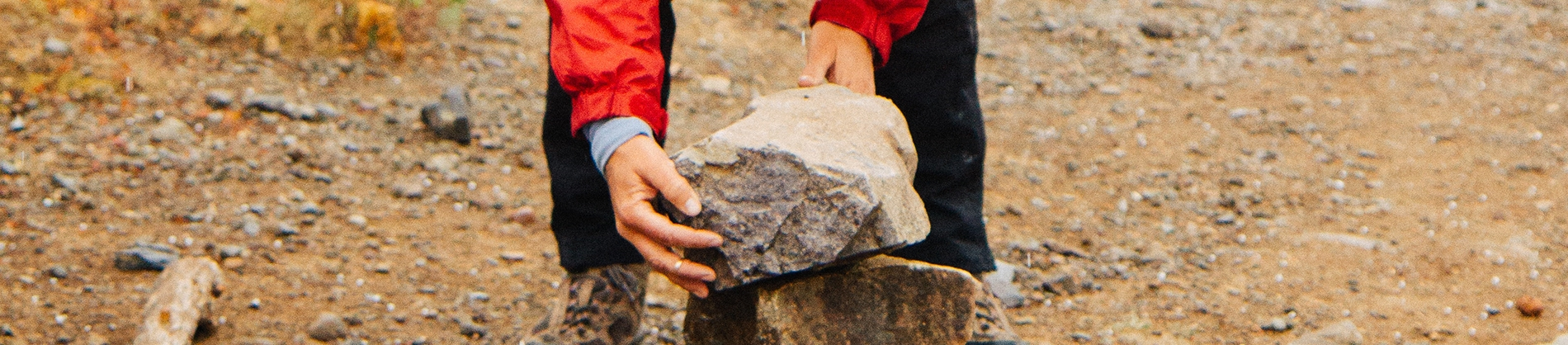 A person picking up a large rock