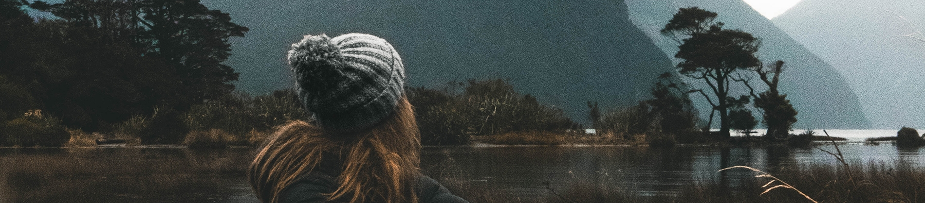 A women in a wooly hat looking out over a lake and mountains