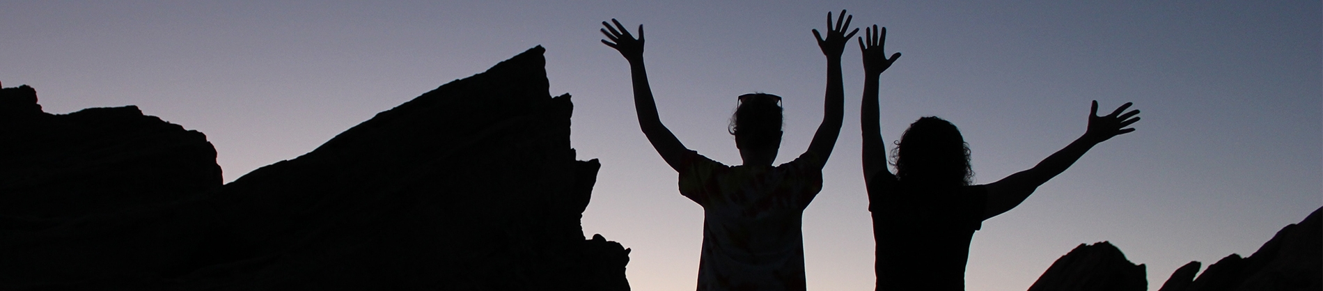 Two women with their hands up in the air