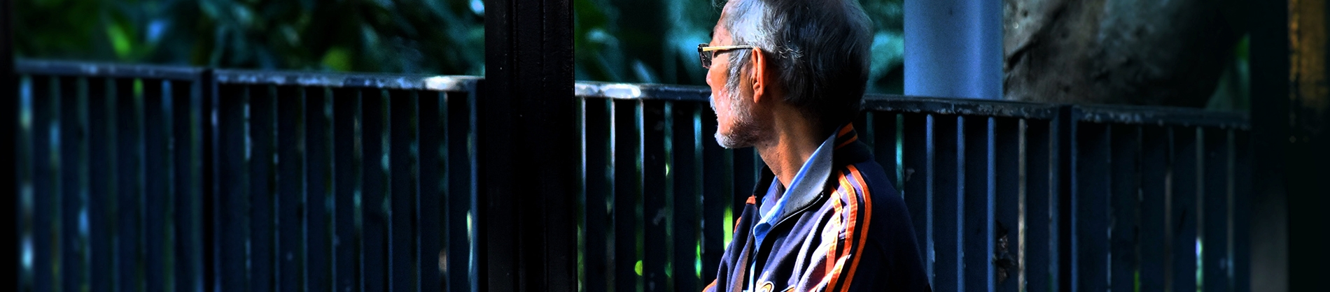 A man sat by some railings looking off into the distance