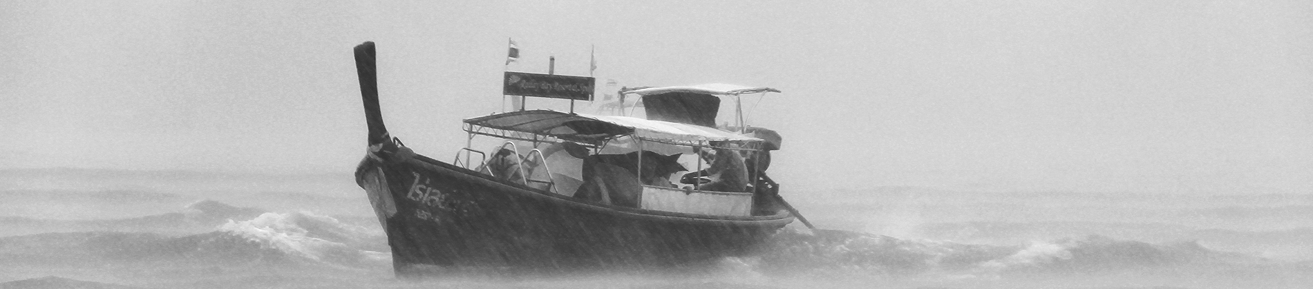 A black and white photo of a boat in the middle of a storm