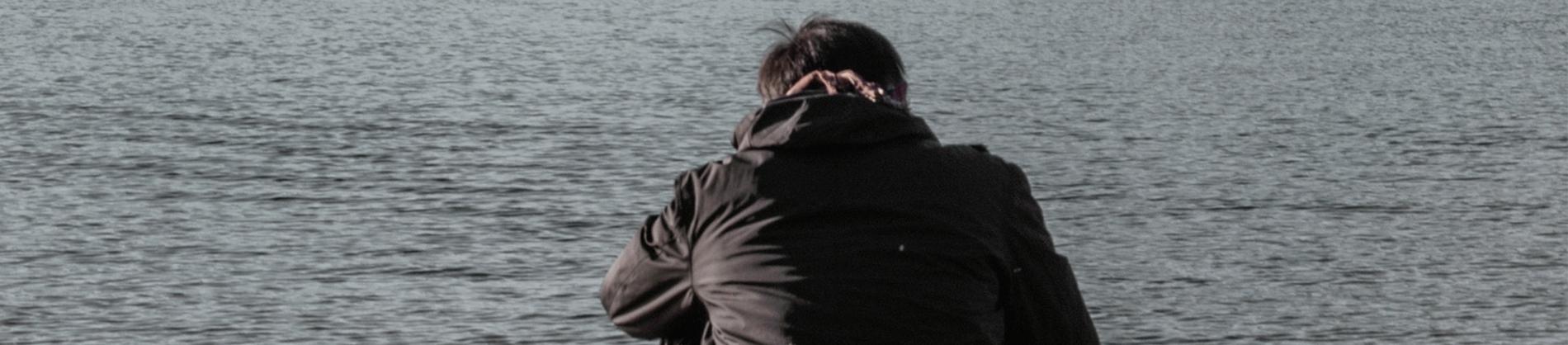A man sat down by a lake