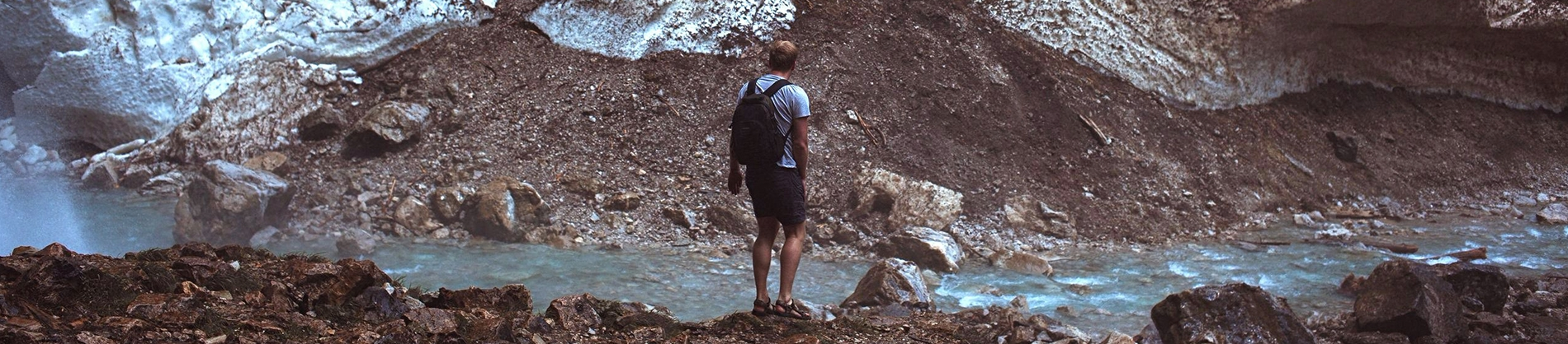 A guy stood on rocks looking over a river onto mountains