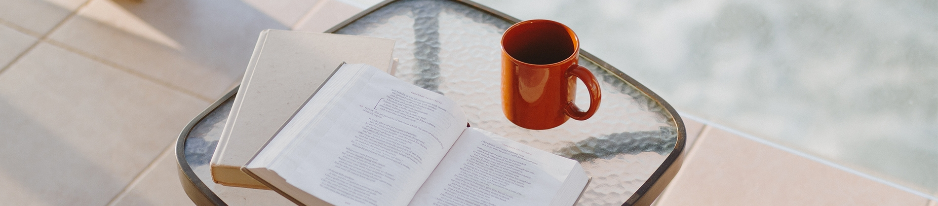 Open bible, notebook and cup of coffee on a glass table by the pool
