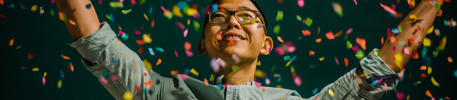 A guy smiling with his arms in the air and confetti falling around him
