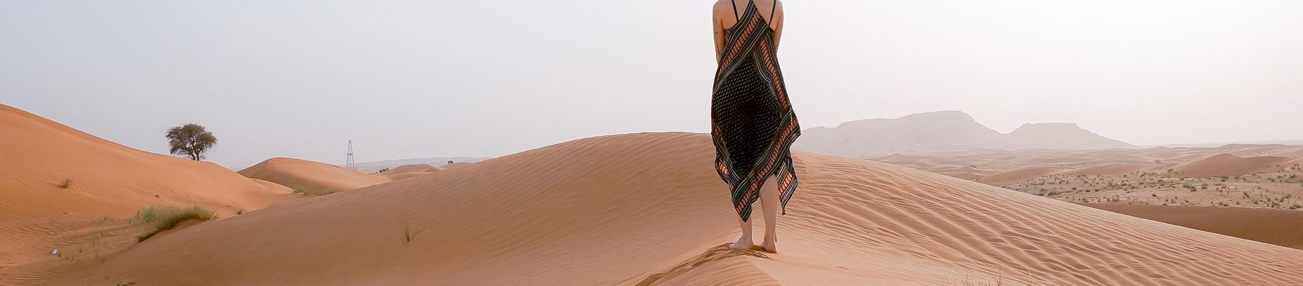 A women walking along sand dunes